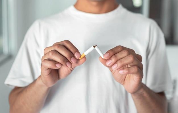 Stop met het roken van sigaretten concept. portret van mooie gebroken sigaret in handen te houden. gelukkig, gezondheidszorgconcept. niet roken.