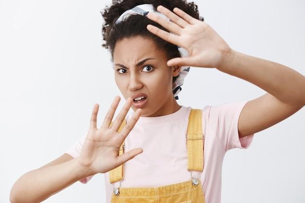 Stop met het rond mijn gezicht te zwaaien. portret van ontevreden en gehinderd geërgerd afro-amerikaanse moderne vrouw in gele overall en hoofdband, bedekt met opgeheven handpalmen, fronsend
