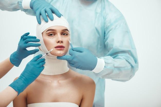 Stop met het verouderen van jonge aantrekkelijke vrouw met hoofd in verband die naar de camera kijkt terwijl artsen bezig zijn