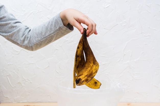 Stop met het verspillen van voedsel. een kinderhand gooit een rotte schil van een banaan in de prullenbak.