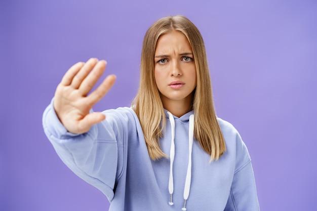 Stop met mij te fotograferen. bezorgde ontevreden jonge vrouw veeleisend einde schieten hand in hand trekken nee en afwijzing gebaar fronsend ernstig en ontevreden over blauwe muur kijken