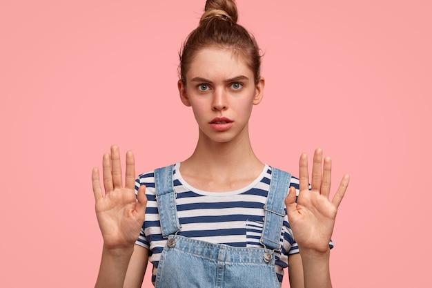 Stop met paniek alsjeblieft! aanbiddelijk ernstig blauwogig vrouwenmodel toont stopbord, houdt palmen vooraan