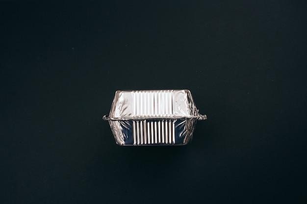 Stop met plastic vervuiling. aluminiumfolie zilveren container voor voedsel op donkere achtergrond, bovenaanzicht. geen plastic voor eenmalig gebruik. een milieuprobleem, eu-richtlijn