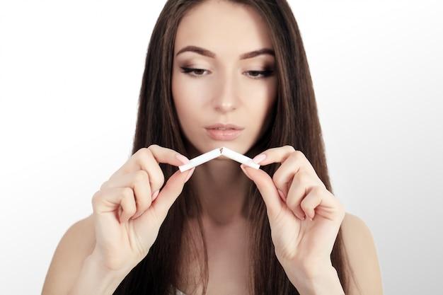 Stop met roken concept. de jonge vrouw sneed sigaretten met schaar het gelukkige glimlachen. focus op hand, schaar en sigaretten