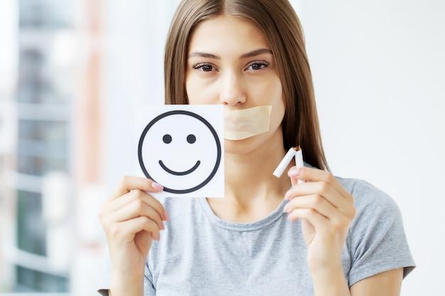 Stop met roken, een jonge vrouw met een verzegelde mond vestigt de aandacht op de schadelijke effecten van roken op de gezondheid