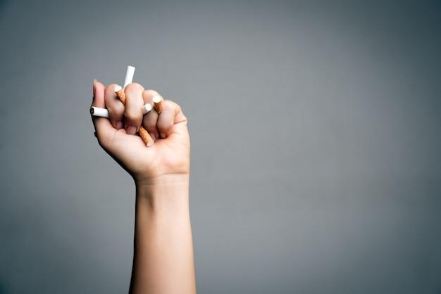 Stop met roken. mensenhand die en sigaretten verpletteren vernietigen