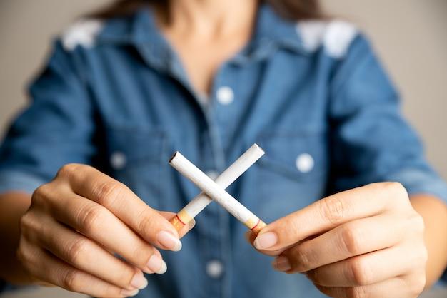 Stop met roken. sluit omhoog vrouwenhand houdend gekruiste sigaretten.