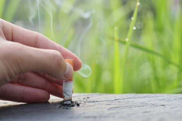 Stop met roken stop met roken concept, met de hand gevallen sigaretten kwamen naar de houten tafel om te stoppen met roken.