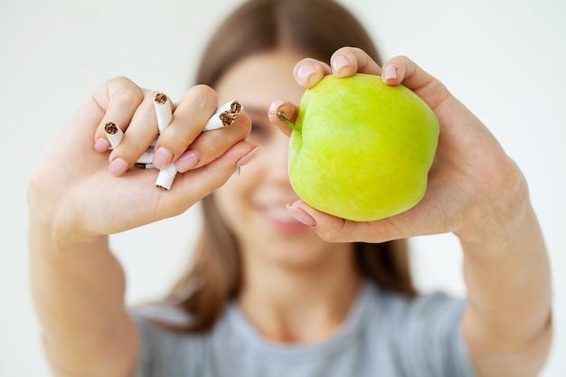 Stop met roken, vrouw met gebroken sigaretten en groene appel in handen.