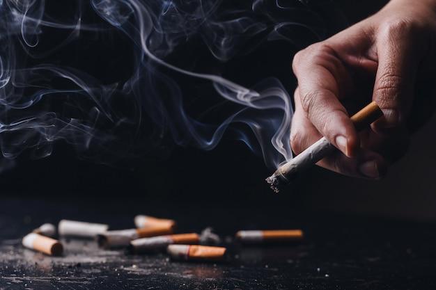 Stop met roken. werelddag zonder tabak. sluit een hand met een verfrommelde, smeulende sigaret met rook. hand rokende sigaret, ongezonde levensstijl