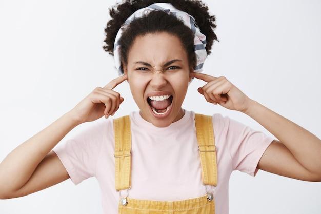 Stop met schreeuwen. portret van verontruste, van streek en beu donkere vrouw in hoofdband en overall, oren bedekkend om ouders niet te horen schreeuwen tegen hen over grijze muur