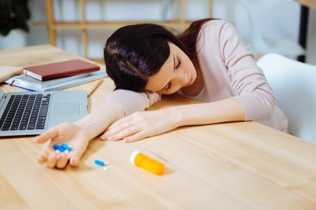 Stop met slapen. zieke vrouwelijke persoon die de ogen gesloten houdt en de tabletten in de rechterhand houdt terwijl ze ze gaat innemen
