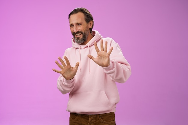Stop nee, kom niet dichterbij. portret ongemakkelijke, onzekere, bange volwassen man met een baard die vraagt: stop genoeg, de handpalmen omhoog, smekend, weiger een stap achteruit, ontevreden, onzeker.