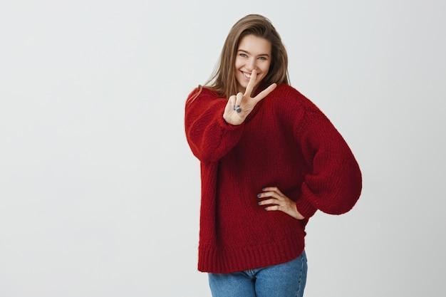 Stop nooit met glimlachen. studio die van positieve mooie kaukasische vrouw is ontsproten die hand naar camera met v-teken trekt, vredesgebaar toont, vriendelijkheid en vreugde uitdrukt, status