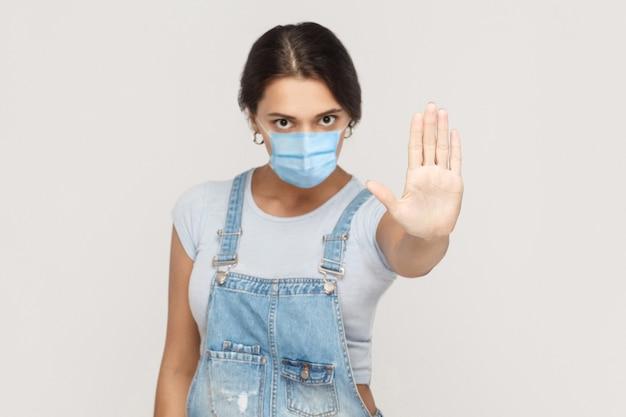 Stop. portret van een boze jonge brunette vrouw met een chirurgisch medisch masker in een denim overall die staat en een stopbord toont met handen, kijkend naar de camera. indoor studio opname geïsoleerd op een grijze achtergrond.