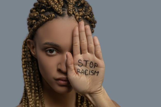 Stop racisme. jonge afro-amerikaanse vrouw die de helft van haar gezicht bedekt met palm met stop racisme belettering