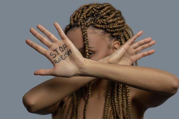 Stop racisme. jonge afro-amerikaanse vrouw die haar gezicht verbergt achter gekruiste handpalmen met stop racisme belettering