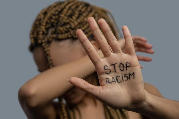 Stop racisme. jonge afro-amerikaanse vrouw met palm met stop racisme belettering, die haar gezicht bedekt met elleboog