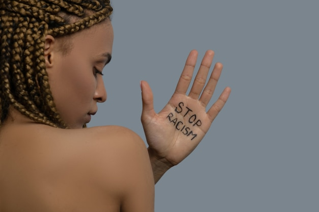 Stop racisme. jonge afro-amerikaanse vrouw rug aan rug, palm met stop racisme letters boven haar schouder, zijwaarts kijkend