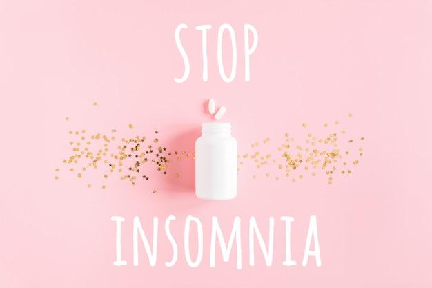 Stop slapeloosheidstekst, twee pillen, witte fles en gouden sterrenconfettien op roze achtergrond.