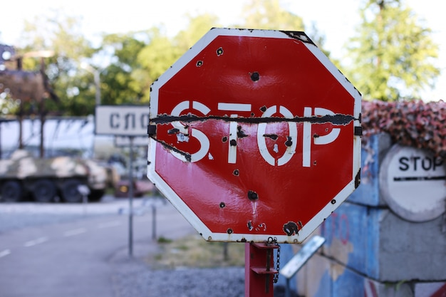 Stop verkeersbord, op het toneel van vijandelijkheden. kogelgaten in metaal.
