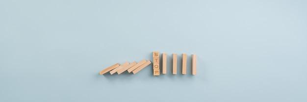 Stopbord in het midden van instortende domino's