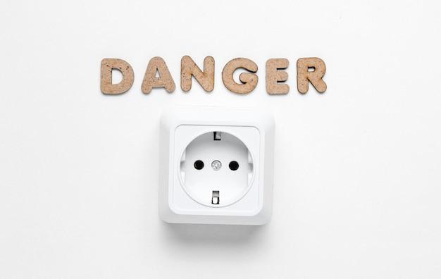 Stopcontact met het woord gevaar op wit