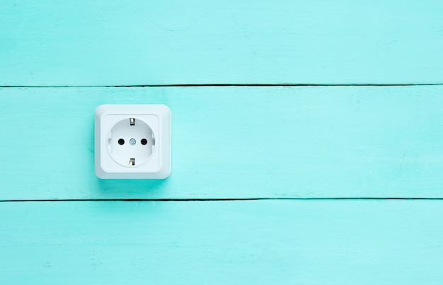 Stopcontact op blauwe houten muur,