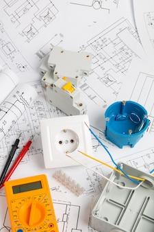 Stopcontact, schakelaar, stroomonderbrekers, snijbox en digitale multimeter. installatie van voedingssystemen met papieren tekeningen