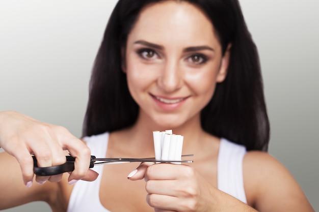 Stoppen met roken. close-up van vrouwelijke handen die een bos van sigaretten houden en hen snijden in de helften met een schaar.