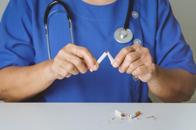 Stoppen met roken, geen tabaksdag, doktershanden die de sigaret breken