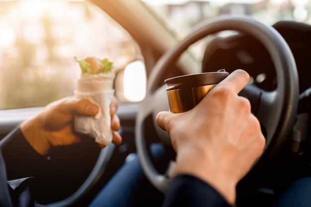 Stoppen voor een hapje. man eet snack in de auto en drinkt koffie of thee. voedsel close-up concept.
