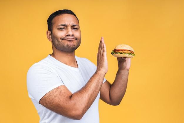 Stopteken. jonge afro-amerikaanse indiase zwarte man eten hamburger geïsoleerd op gele achtergrond. dieet concept.