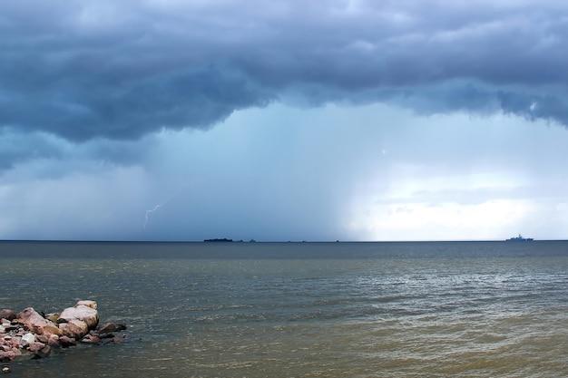 Storm wolken regen en bliksem over de zee horizon