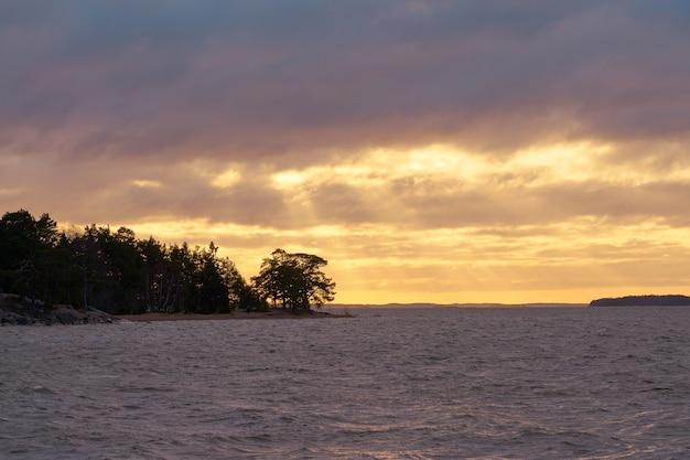 Stormachtig golvend zeewater op een zonsondergang met bewolkte hemel