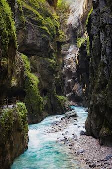 Stormachtige bergrivier stroomt door in duitsland in de partnach-grot. het zonlicht schijnt in de donkere kloof.