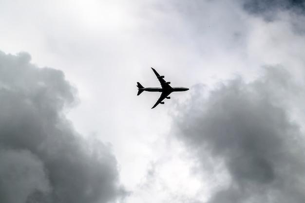 Stormachtige wolken in donkere hemel en een passagiersvliegtuig. jet aircraft op dramatische hemelachtergrond. humeurig cloudscape.