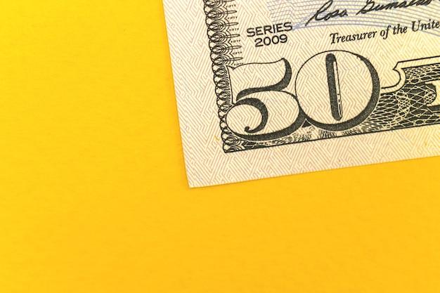 Stort geld met biljetten van vijftig dollar, kantoorbureaublad met gele achtergrond en kopieer ruimtefoto