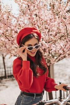 Stout meisje met golvend haar neemt haar bril af en kijkt in de camera. aantrekkelijke brunette vrouw in baret, rode trui en spijkerbroek poseren met fiets tegen sakura