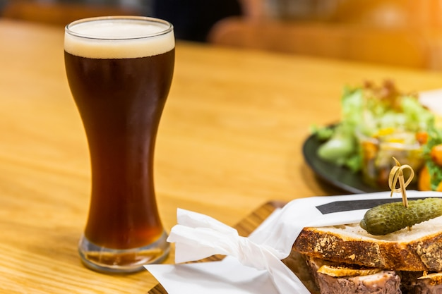 Stout (zwart bier) met schuim in een drinkglas op een houten tafel met vervagen voedsel