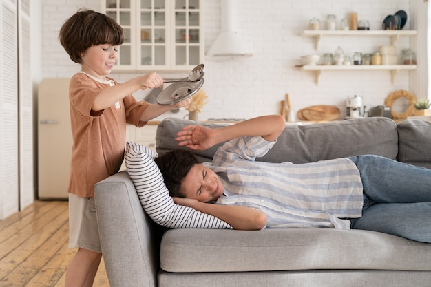 Stoute kleine jongen die keukengerei rommelt als gestresste en vermoeide moeder die op de bank in de woonkamer slaapt