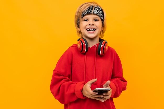Stoute schooljongen in een rode hoodie met een telefoon in zijn handen, een jongen met een koptelefoon op een oppervlak van een oranje muur