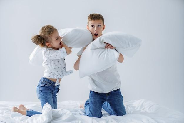 Stoute tweeling vriendelijk vechten met kussens op het bed