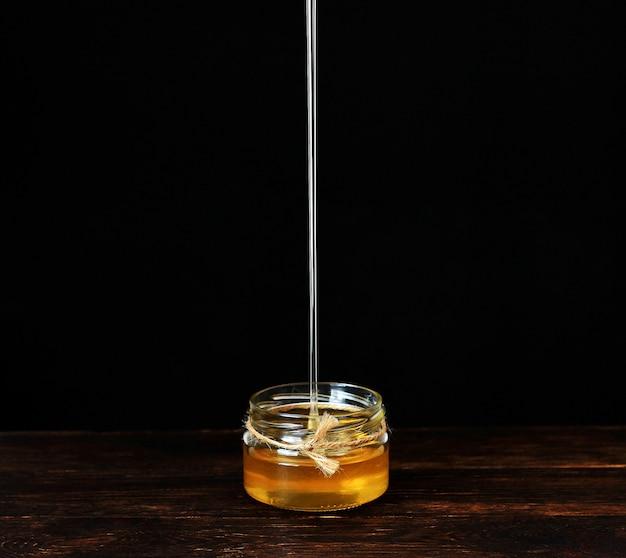 Straal van honing gieten in een glazen pot, druipende vloeibare honing, lekker goudgeel. bruine houten tafel tegen zwart. copyspace.