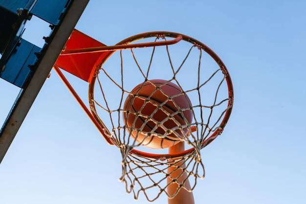 Straat basketbal slam dunk competitie, close-up van de bal die in de hoepel valt. Premium Foto