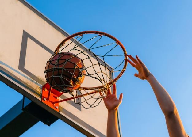 Straat basketbal slam dunk competitie, close-up van handen opknoping op de hoepel.
