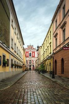 Straat bij regenachtig weer die leidt naar de kerk, stadscentrum: poznan / polen - 27 september 2020