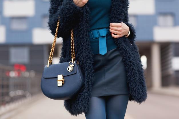 Straat, heldere stijl. een jong meisje in een blauwe bontjas met een handtas in hakken. details.