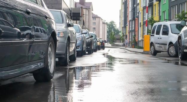 Straat in een stad zonder mensen met geparkeerde auto's bij regenachtig weer. regen op de weg. regen en auto's. achtergrond van geparkeerde auto's op een regenachtige stadsstraat. symmetrisch geparkeerde auto's.
