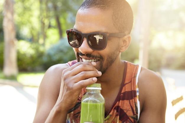 Straat levensstijl concept. jonge lachende afro-amerikaanse man met snor en korte baard vers sap drinken tijdens de date, terloops gekleed in kleurrijke tank top en trendy tinten of zonnebril